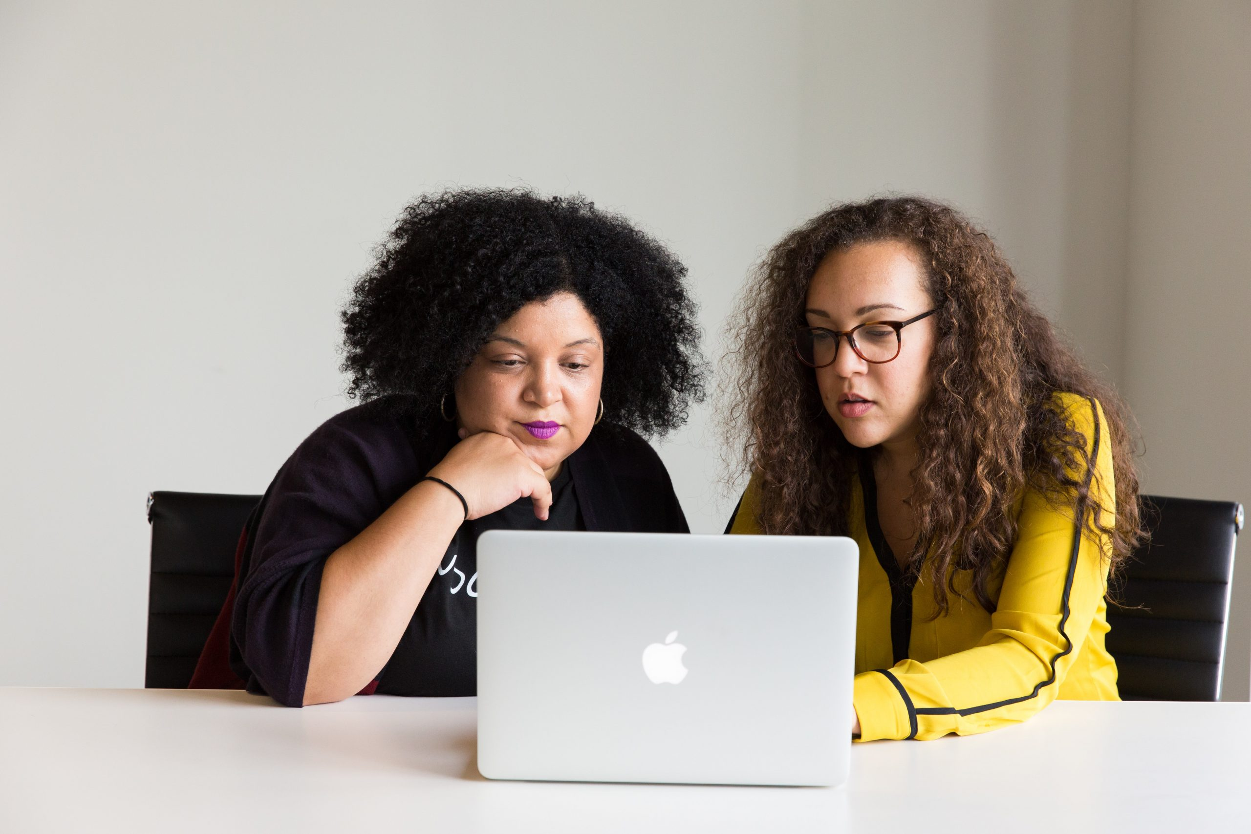 two women working on a laptop together